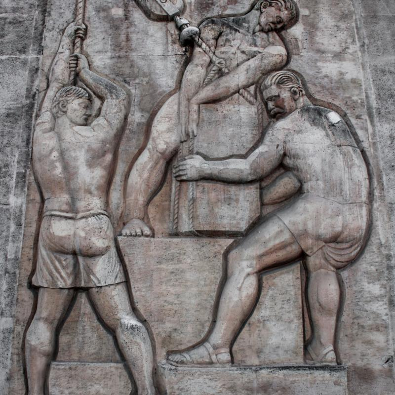 This socialist style relief was made by Medgyessy Ferenc in 1950. It's title is Hídépítők (Bridge-builders). It was released on the opening ceremony of the Árpád bridge in Budapest that is near to this building. This is why the relief illustrates workers on a bridge.